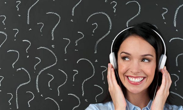 Attractive woman listening to music with question marks on a blackboard with copy space